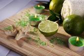 Spa composition with lime, towel and candles on bamboo mat and color wooden background — Stock Photo