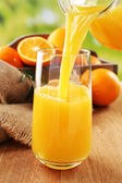 Pouring orange juice from glass carafe, on wooden table and bright background — Stock Photo