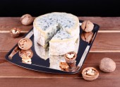 Blue cheese with nuts and blade on metal tray and wooden table and dark background — Stock Photo