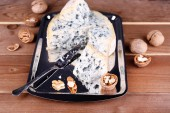 Blue cheese with nuts and blade on metal tray and wooden table background — Stock Photo