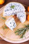 Blue cheese with sprigs of rosemary and oranges on board and wooden table background — Stock Photo