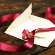 Envelope with love letter, vinous ribbon and dried rose on rustic wooden table background — Stock Photo #62951505