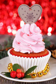 Cup-cake with cream on saucer and Christmas decoration on wooden table and shine brightly background — Stock Photo