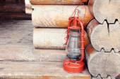 Kerosene lamp on wooden hose background — Stock Photo