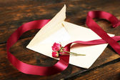 Envelope with love letter, vinous ribbon and dried rose on rustic wooden table background — Stock Photo