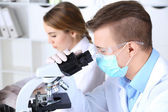 Young female and male scientists  with microscope in laboratory — Stock Photo