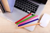 Laptop with computer mouse and colorful pencils on wooden table background — Stock Photo