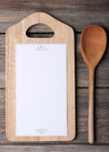 Cutting board with menu sheet of paper on rustic wooden planks background — Stockfoto