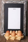 Menu board with eggs on rustic wooden planks background — Stock Photo