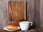 Cutting board with cup of coffee and croissant on wooden planks background — Stock Photo