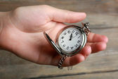 Silver pocket clock in hand on wooden background — Stock Photo