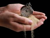 Silver pocket clock in hands and sand flowing away on black background — Foto de Stock