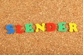 Slender word on cork board background — Stockfoto
