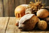 Different bread on table on wooden background — Stockfoto