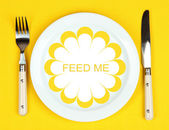 Plate with text Feed Me, fork and knife on tablecloth background — Foto Stock