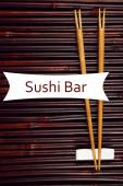 Pair of chopsticks and Sushi Bar text on bamboo mat background — 图库照片