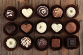 Delicious chocolate candies on wooden background — Stock Photo