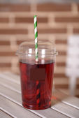 Pomegranate juice in fast food closed cup with tube on wooden table and brick wall background — Stock Photo