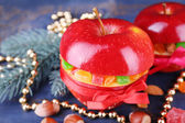Red apples stuffed with dried fruits with cinnamon, sprig of fir tree and nuts on color wooden table background — Stock Photo