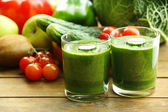 Green fresh healthy juice with fruits and vegetables on wooden table background — Stock Photo
