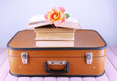 Vintage suitcase with pile on books on patterned surface and light background — Stock Photo