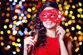 Beautiful girl with masquerade mask and glass of champagne on bright background — Stock Photo