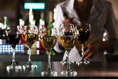Bartender working at counter on bar background — Foto Stock