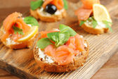 Canapes with salmon and black olive — Stock Photo