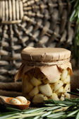 Canned garlic in glass jar and wicker mat and rosemary branches, on wicker mat background — Stock Photo