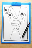 Scheme basketball game on clip board paper with marker and wooden table background — Zdjęcie stockowe