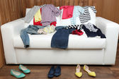 Colorful clothing on white sofa and female shoes on wooden planks background — Stock Photo