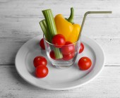 Vegetables in glass with tube on plate and on color wooden planks background — Stock Photo