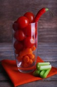 Vegetables with chili pepper in glass on napkin and rustic wooden background — Stock Photo