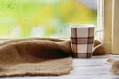 Cup of hot drink with sackcloth on windowsill on rain background — Stock Photo