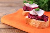 Rye toasts with herring and beets on napkin on wooden table — Stock Photo