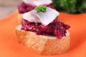 Rye toasts with herring and beets on napkin close up — Stock Photo
