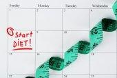 Diet concept - measure tape on calendar, close up — Stock Photo