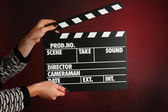 Movie clapper in female hand on dark color background — Stock Photo