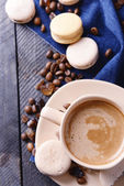 Gentle colorful macaroons and  coffee in mug on wooden table background, top view — Stock Photo