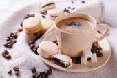 Gentle colorful macaroons and  coffee in mug on color wooden  background — Stock Photo