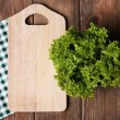 Cutting board with lettuce on wooden planks background — Stock Photo #63168181