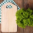 Cutting board with lettuce on wooden planks background — Stock Photo #63168185