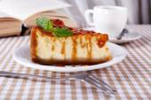 Cheese cake and cup of coffee on tablecloth on curtain background — Stock Photo