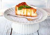 Cheese cake on paper napkin on plate on wooden background — Stock Photo