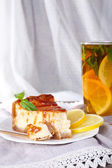 Cheese cake in plate and herbal tea on napkin on curtain background — Stock Photo