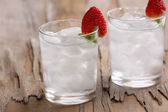 Glasses with ice cubes on wooden table — Stock Photo