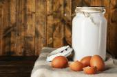 Milk can with eggs and eggshell on rustic wooden background — Stock Photo