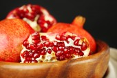 Juicy ripe pomegranates in wooden bowl, on dark background — Stock Photo