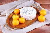 Blue cheese with oranges on metal tray on burlap cloth and wooden table background — Stock Photo