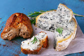 Blue cheese with sprigs of rosemary and bread on sheet of paper and color wooden table background — Foto de Stock